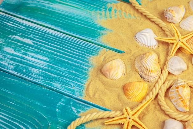 Морской песок и морские раковины на синем деревянном полу