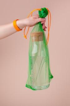 Сетчатые мешки с многоразовой стеклянной бутылкой для воды. нулевая концепция отходов