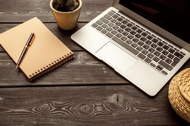 空白のノートブックとラップトップのコーヒーカップのオフィステーブル