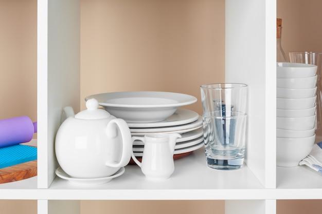 食器やマグ、木製の棚にキッチン用品