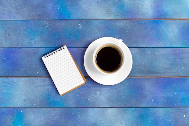 チェックリストのモックアップ、青い木のコーヒーカップと空のメモ用紙。オフィス、作家または研究コンセプト