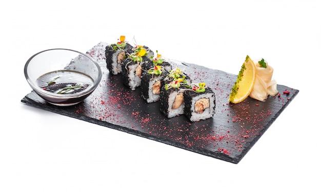 Черная прямоугольная тарелка с суши, изолированная на белом