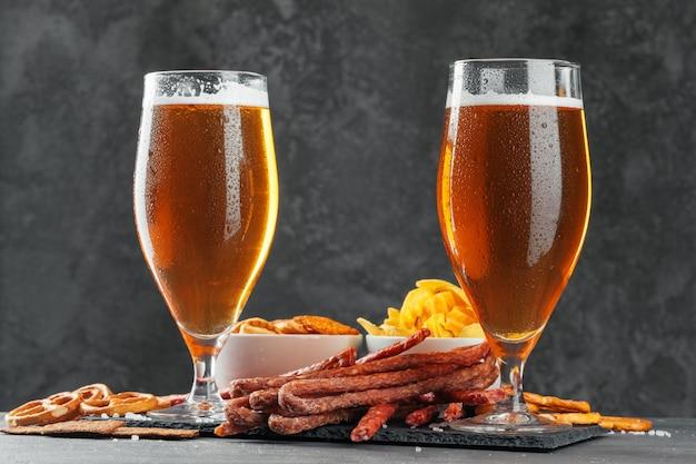 ビールと食欲をそそるビールスナックセット。ビールのジョッキ、ソーセージと木の板を持つテーブル