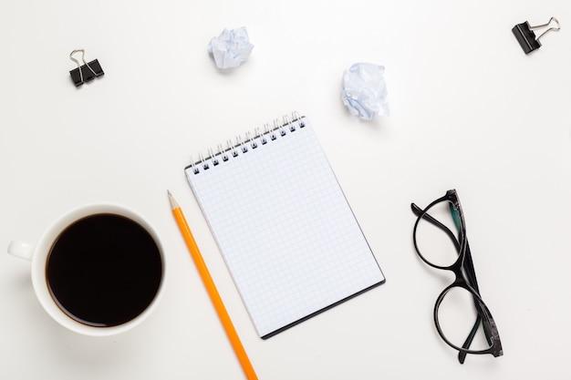 コーヒーカップ、メモ帳、メガネ、鉛筆