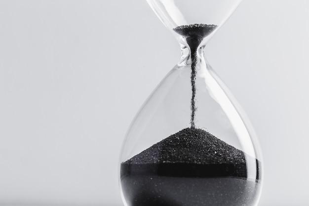 黒い砂と砂時計のクローズアップ