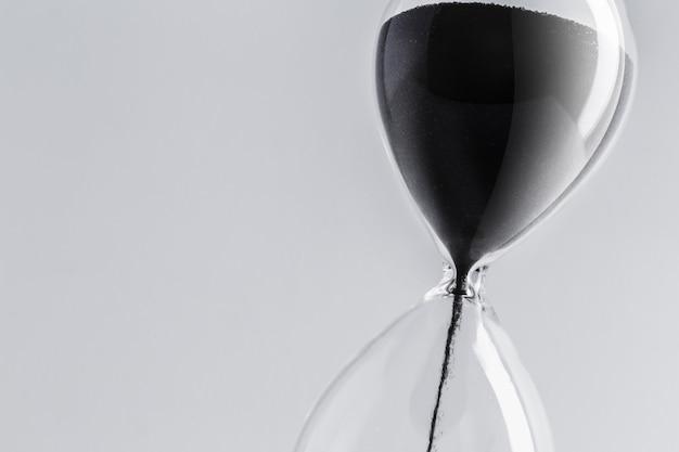 Крупным планом песочные часы с черным песком