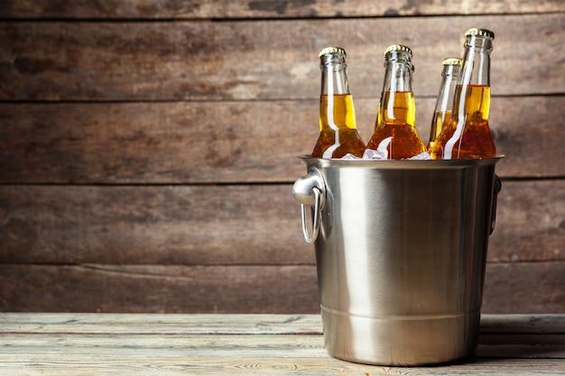 Холодные бутылки пива в ведре на деревянном