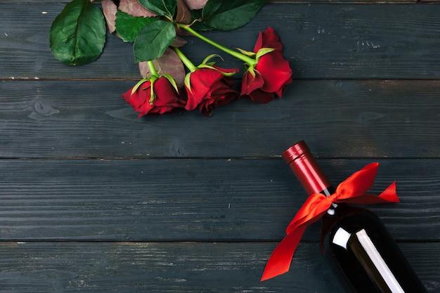 Цветки красной розы, вино и подарочная коробка на деревянном столе.