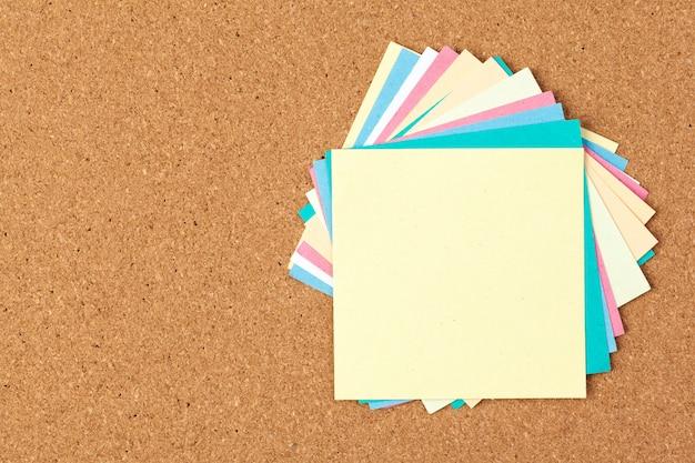 いくつかのカラフルな空白のノートとコルク板