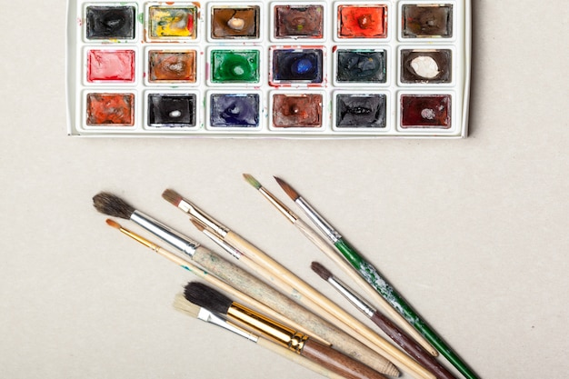 水彩画用品、ブラシ、カラフルな鉛筆の平面図。