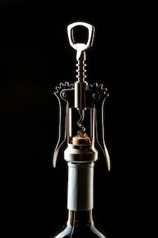 暗闇の上のワインとコルク抜きのボトル