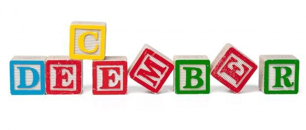 Красочный алфавит блоков. слово декабрь, изолированные на белом