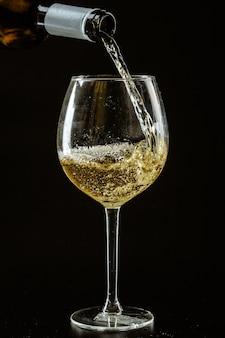 Белое вино наливают в бокал на темном
