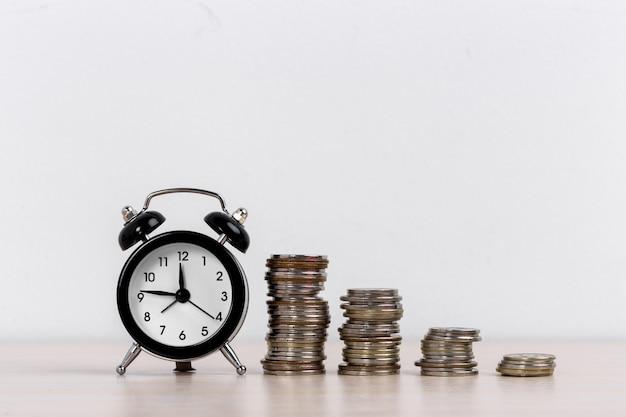 目覚まし時計と白い表面のコイン