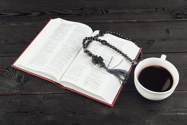 Библия и распятие на старый деревянный стол с чашкой кофе