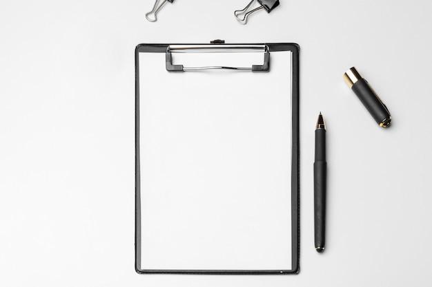 白いシートとペン、白で隔離されるクリップボード。上面図