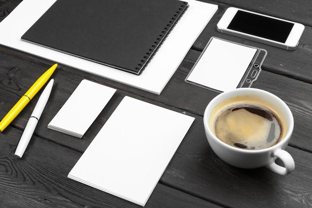 木製のテーブルに設定されている空白の企業文具。ブランディングのモックアップ。