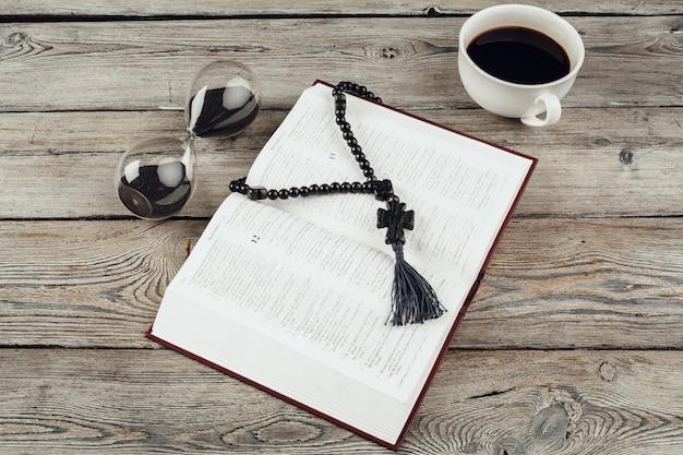 Песочные часы и открытая библия с чашкой кофе