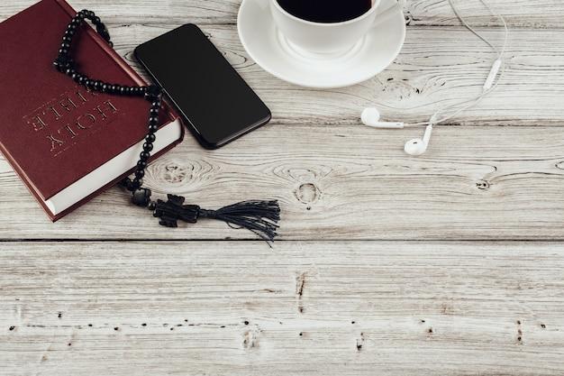 Библия и смартфон с черной кофейной чашкой на деревянной поверхности.