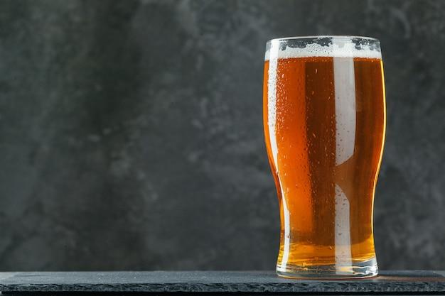 Один стакан пива крупным планом на фоне темного камня