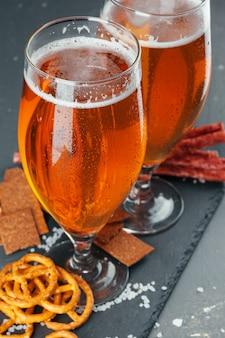 Пиво и аппетитные пивные закуски. стол с кружкой пива, деревянная доска с сосисками