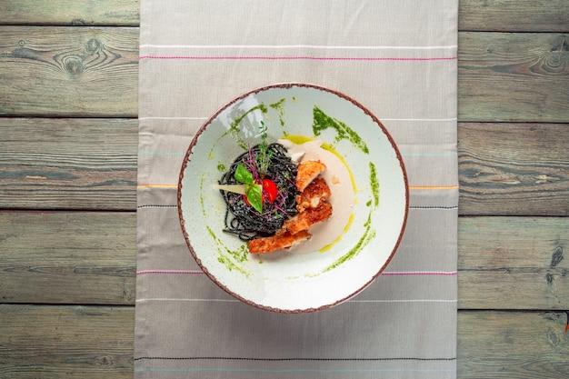 Свежая черная паста тальолини с курицей в травах на руколе и помидорах