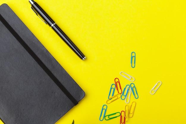 黄色のテーブルの上の文房具。創造的で教育的なカラフルなテンプレート
