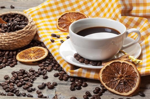 一杯のコーヒーとテーブルの上のコーヒー豆