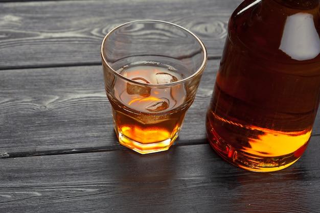 ボトルと木製のウィスキーのグラス