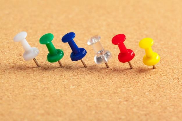 Группа канцелярских кнопок, закрепленных на пробковой доске в ряд крупным планом зрения
