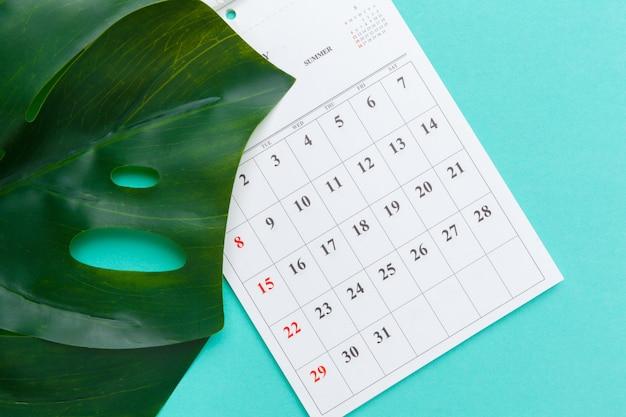 Плоский вид сверху рабочего стола в стиле офисных принадлежностей с календарем