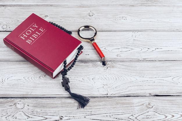 聖書と十字架、白い木製のテーブル