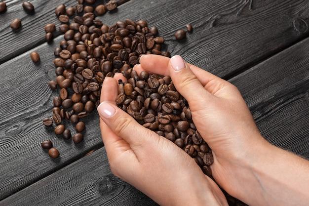 Персона держа кофейное зерно кофе на деревянном столе
