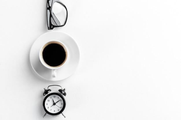 Натюрморт, винтажный будильник и чашка кофе на белом столе