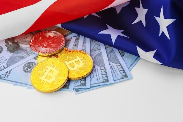Биткойн физические монеты на американском флаге с долларами