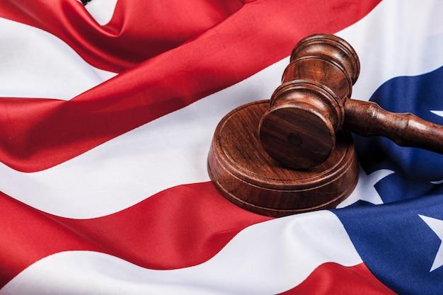 Деревянный молоток и флаг сша на столе крупным планом