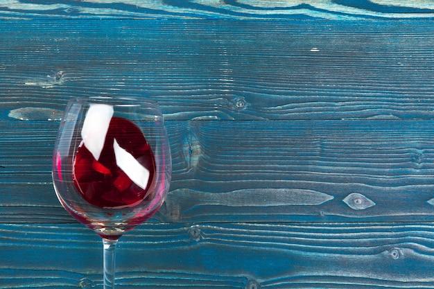 木製の壁の背景に木製のテーブルに赤ワインのゴブレット