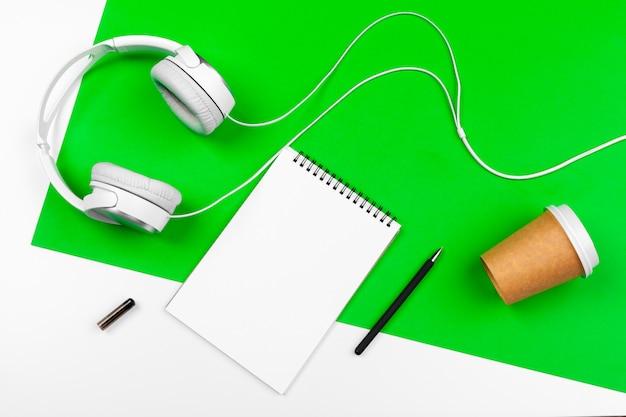 明るい緑の背景にコード付きの白いヘッドフォン