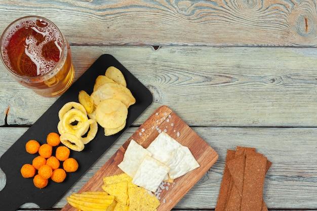 Лагер пиво и закуски на деревянный стол.