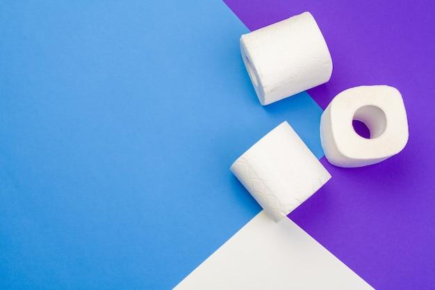 Рулоны раскрытой туалетной бумаги на синем фоне. плоская планировка, вид сверху