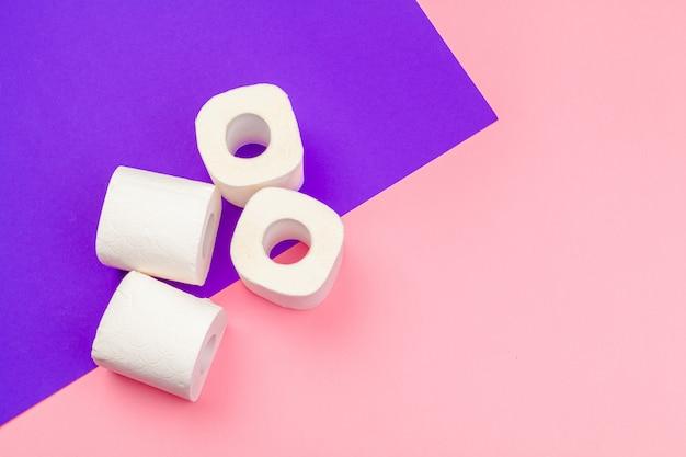 Рулоны белой туалетной бумаги на ярком фоне цветных блоков