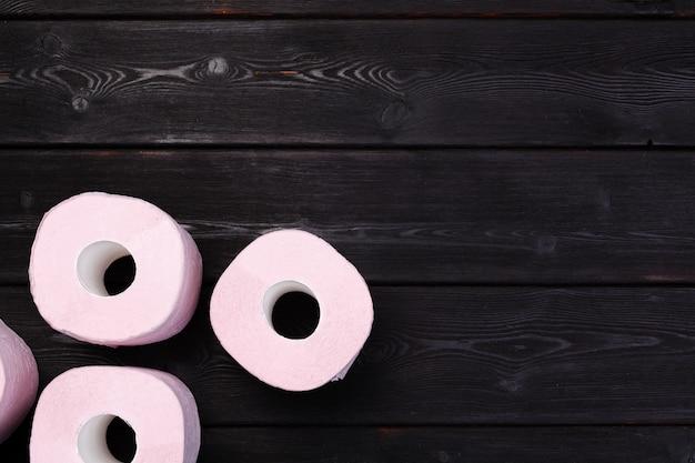 Пастельные розовые рулоны туалетной бумаги на черном деревянном столе