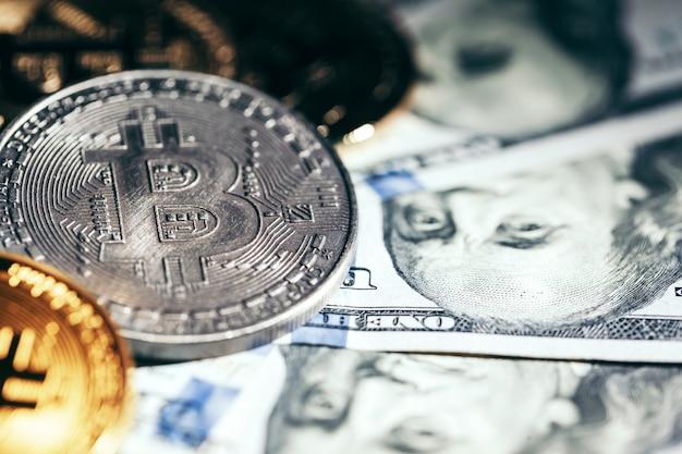 Золотые монеты биткойн на бумажных долларах