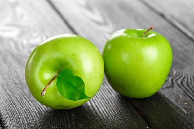 Зеленое яблоко на деревянном фоне