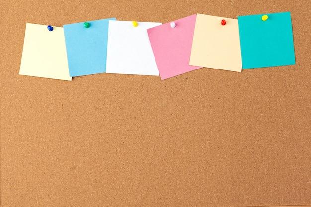 Пробковая доска с несколькими красочными пустыми нотами с булавками