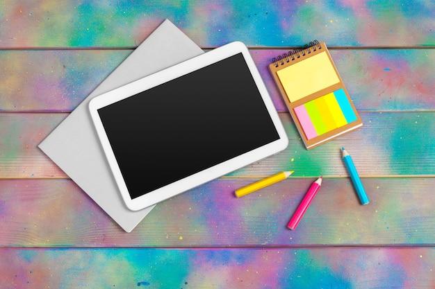Современная пустая цифровая таблетка с бумагами и ручка на деревянном поверхностном столе.