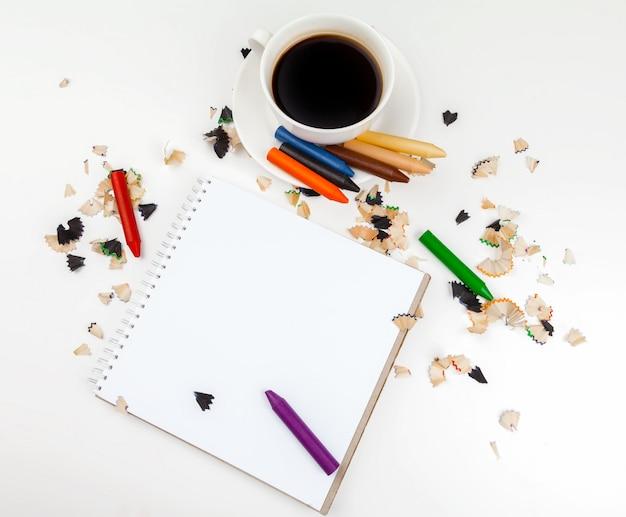 コーヒーカップと鉛筆削りのとがった鉛筆
