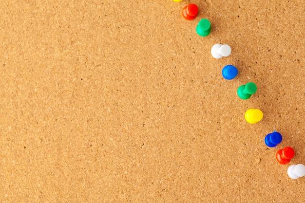 Группа канцелярских кнопок закреплена на пробковой доске