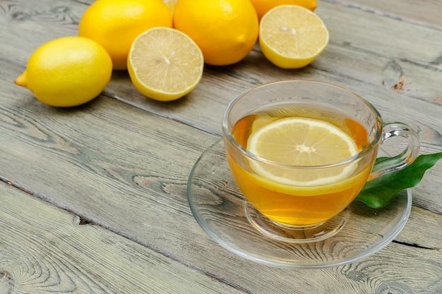 Лимонный чай с лимоном и лаймом на деревянной поверхности стола