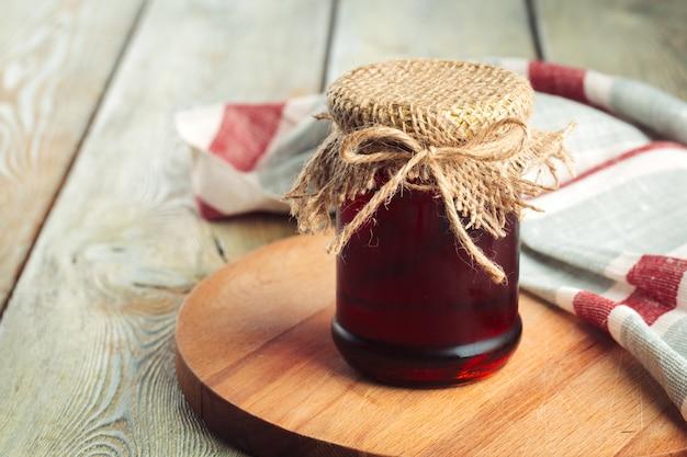 蜂蜜の背景。木製の背景にガラスの瓶に甘い蜂蜜。